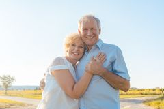 Romantic elderly couple enjoying health and nature in a sunny da. Low-angle view of a romantic elderly couple enjoying health and nature while standing together stock photos