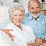 Romantic elderly couple. Sitting close together on a sofa in their living room in a loving embrace smiling at the camera Stock Image