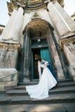 Romantic elegant newlywed couple posing near baroque column church.  Stock Photography