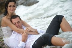 Romantic embrace (bride and groom of the sea). Beautiful couple posing in the sea water Stock Image