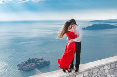 Romantic embracing couple beside blue sea in front of Sveti Stef Royalty Free Stock Photos