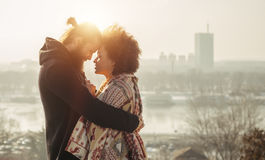 Romantic embracing loving couple. Falling in love. Romantic embracing loving couple enjoying the sunset in front of the city panorama. Falling in love Royalty Free Stock Photo