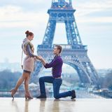 Romantic engagement in Paris. Men proposing to his beautiful girlfriend near the Eiffel tower Royalty Free Stock Photos