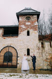 Romantic enloved newlywed couple posing near old castle walls at winter background Royalty Free Stock Images