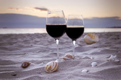 Romantic evening. Romantic beach evening on the sunset: two glasses of wine, candles, shells, valentines day Royalty Free Stock Image
