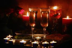 Romantic evening by candlelight. Champagne, fruit, candles and a romantic evening royalty free stock image