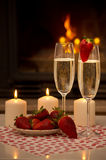 Romantic evening by the fireplace. Champagne, strawberries, candles and a romantic evening by the fireplace Stock Photography