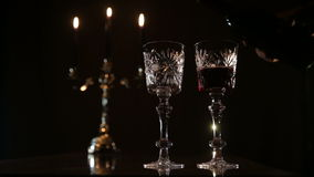Romantic evening with wine. Arm pours wine from a bottle into a beautiful wine glasses.Red wine bottle, two wine glasses,burning candles in a chandelier.Wine stock video footage