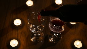 Romantic evening with wine. Arm pours wine from a bottle into a beautiful wine glasses.Red wine bottle, two wine glasses,burning candles in a chandelier.Wine stock footage