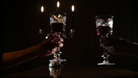 Romantic evening with wine. Hands take glasses of wine.Two wine glasses,burning candles in a chandelier.Wine glasses on the table,and burning candles in a stock video