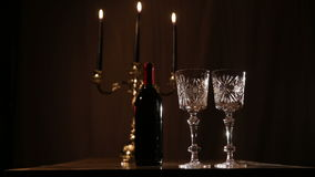 Romantic evening with wine. Red wine bottle, two wine glasses,burning candles in a chandelier.Wine glasses on the table, a bottle of red wine and burning stock video
