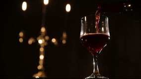 Romantic evening with wine. Red wine poured in a glass.Red wine bottle, two wine glasses,burning candles in a chandelier.Pouring red wine into the glass.Wine stock footage