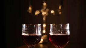 Romantic evening with wine. Two red wine glasses.Wine glasses on the table,and burning candles in beautiful chandelier.Romantic atmosphere with wine glasses and stock video