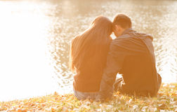 Romantic evening. Young couple sitting near lake in evening heads together rear view Royalty Free Stock Photo