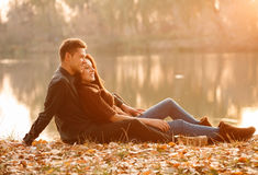 Romantic evening. Young couple sitting near lake smiling having good time sunset Stock Photo
