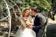 Romantic fairy-tale wedding couple bride and groom hugging in ma. Gical cinderella white carriage Royalty Free Stock Photos