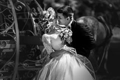 Romantic fairy-tale wedding couple bride and groom hugging in ma. Gical cinderella white carriage b&w Royalty Free Stock Images