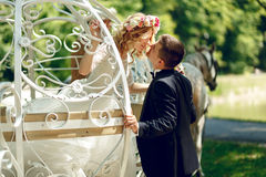 Romantic fairy-tale wedding couple bride and groom kissing in ma. Gical cinderella white carriage Royalty Free Stock Photo