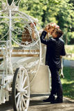 Romantic fairy-tale wedding couple bride and groom kissing in ma. Gical cinderella white carriage Stock Photo