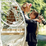 Romantic fairy-tale wedding couple bride and groom kissing in ma. Gical cinderella white carriage Stock Image