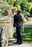 Romantic fairy-tale wedding couple bride and groom kissing in ma. Gical cinderella white carriage Royalty Free Stock Photography