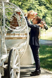 Romantic fairy-tale wedding couple bride and groom kissing in ma. Gical cinderella white carriage Royalty Free Stock Images