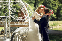 Romantic fairy-tale wedding couple bride and groom kissing in ma. Gical cinderella white carriage Stock Images