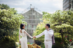 Romantic fairytale married couple in white clothes holding hands Stock Photo