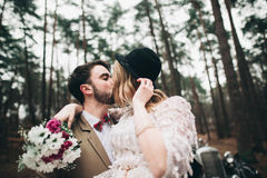 Romantic fairytale wedding couple kissing and embracing in pine forest near retro car. Royalty Free Stock Images