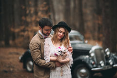 Romantic fairytale wedding couple kissing and embracing in pine forest near retro car. Royalty Free Stock Photography