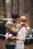 Romantic fairytale wedding couple kissing and embracing in pine forest near retro car. Royalty Free Stock Image