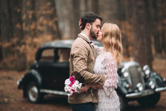 Romantic fairytale wedding couple kissing and embracing in pine forest near retro car. Royalty Free Stock Photo