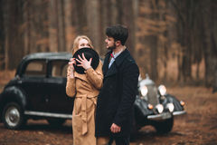 Romantic fairytale wedding couple kissing and embracing in pine forest near retro car. Stock Photos