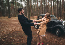Romantic fairytale wedding couple kissing and embracing in pine forest near retro car. Stock Image