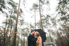 Romantic fairytale wedding couple kissing and embracing in pine forest near retro car. Stock Photography