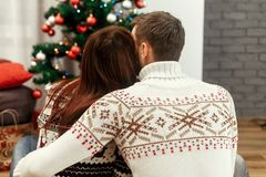 Romantic family couple in fashionable white sweaters hugging while looking at decorated christmas tree, greeting card concept wit royalty free stock photos