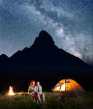 Romantic family tourists covered with a plaid sitting together near campfire and shines tent at night stock photos