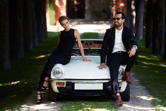 Romantic and fashionable couple posing on luxury cabriolet car outdoors in summer stock photos
