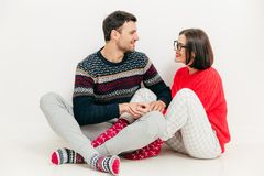 Romantic female and male hold hands together, look at each other. With love, have good relationship, wears knitted sweaters, have positive expressions, isolated royalty free stock photo