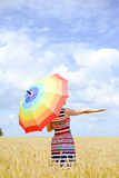 Romantic female with rainbow umbrella in the wheat. Happy lady hiding from the burning sun behind the multi-coloured rainbow umbrella in stripped summer dress Stock Image