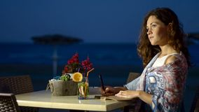 Romantic female writer thinking her new book, relax at seaside restaurant. Stock photo royalty free stock photos