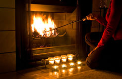 Romantic fireplace. Woman in red sweater stoking a fire in the fireplace with candles burning in front Stock Photos