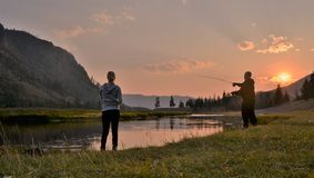 Romantic fishing during sunset. Young couple fly fishing near the river in a warm evening during sunset Royalty Free Stock Photography