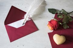 Red love letter with goose feather and rose royalty free stock photo