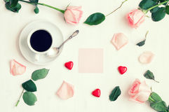 Romantic flat lay still life. Cup of coffee, peach roses, pink sheet of note, heart shaped candies in retro tones Stock Images