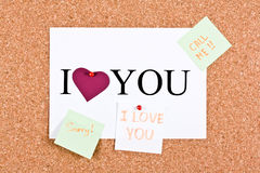Romantic forgiveness. Cork board and a sheet with the words I love you, sorry, call me stock photo