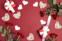 Romantic frame of gifts, rose flowers and decorative hearts on red background. Place for text, top down composition. St. Valentines Day concept royalty free stock images