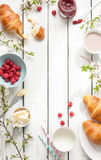 Romantic french or rural breakfast with croissants, jam and raspberries on white. Romantic french or rural breakfast - cocoa, milk, croissants, jam, butter and Stock Image