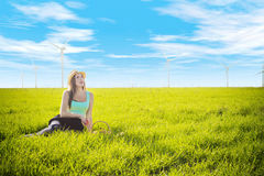 A romantic Frenchwoman enthusiastically looks at wind generators. A romantic Frenchwoman in a hat with a basket of fruit enthusiastically looks up at the wind Stock Image