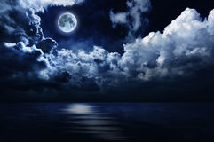 Romantic full moon and night sky over water. Brilliant full moon and cloudy night sky reflecting in still waters Royalty Free Stock Image